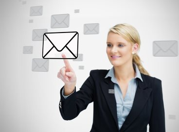 Businesswoman standing while touching an email symbol and smiling