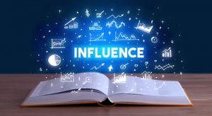 INFLUENCE inscription coming out from an open book, business con